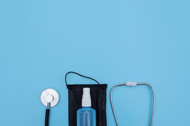 Медицинское оборудование для профилактики коронавируса на голубой стене. стетоскоп, медицинская маска и дезинфицирующее средство. коронавирус, грипп, концепция медицины.