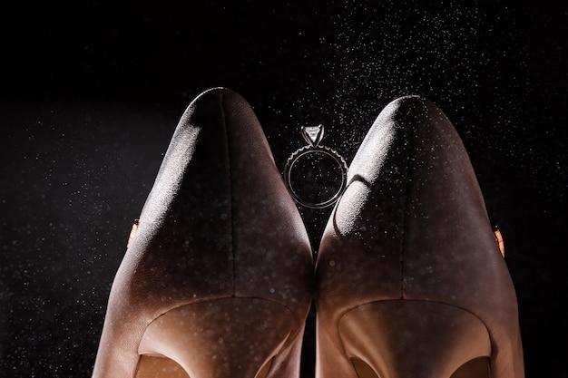Обручальное кольцо между свадебной обуви на темном фоне