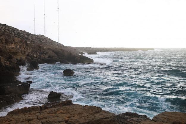 Волны ударяются о скалистые утесы на пляже, расположенном на кипре