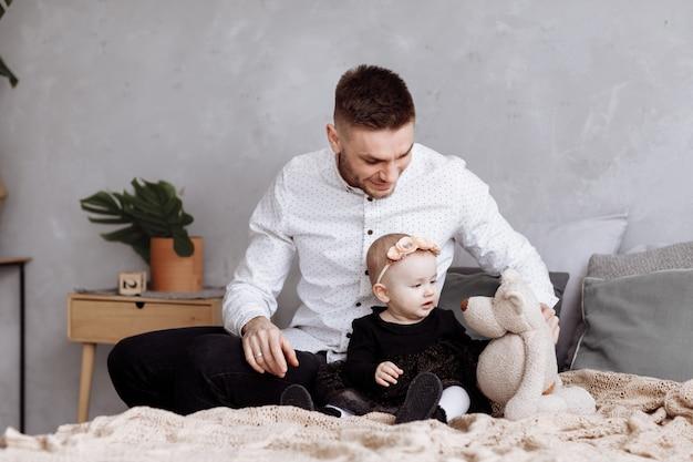 Красивый молодой папа и его милый ребёнок сидят и играют с плюшевым медвежонком на кровати дома.