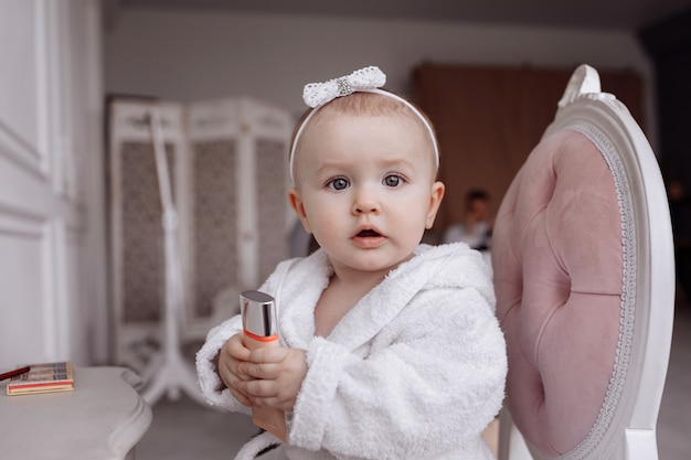 バスローブのかわいい女の子の肖像画がやっていると自宅のカメラで見ています。
