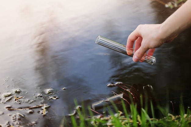 Ученый и биолог гидробиолог отбирает пробы воды для анализа на открытом воздухе.