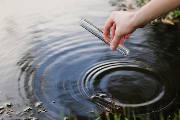 Ученый и биолог гидробиолог отбирает пробы воды для анализа.