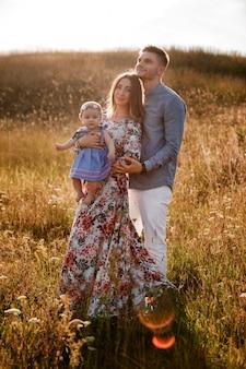 Мама, папа и маленькая девочка с удовольствием на открытом воздухе в траве в летний день. день матери, отца и ребенка. счастливая семья на прогулке.