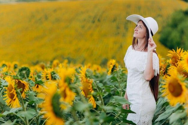 夏に咲くひまわり畑の美しい若い女性。白いドレスと帽子の長い髪を持つスタイリッシュな女の子。夏休み