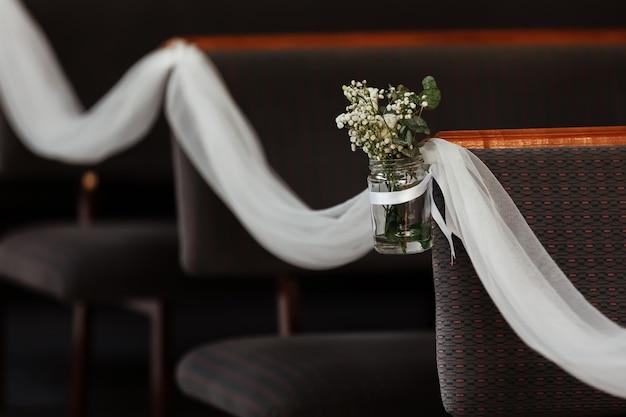 結婚式のために教会で花で飾られた椅子。教会の通路の配置。セレクティブフォーカス
