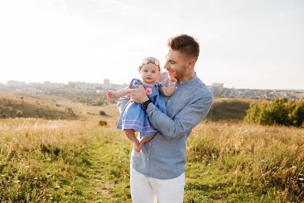 Счастливый улыбающийся молодой отец и маленькая дочь в его руках весело на открытом воздухе в летний день. концепция семьи отцы и детский день