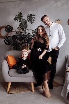 Портрет красивых молодых родителей и их милая маленькая дочь обнимает и улыбается в помещении. день матери, отца, ребенка. понятие семьи. семейный вид