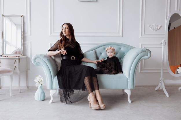 Счастливая молодая мама на стильном диване отдыхает с маленькой дочкой в черных платьях и позирует, улыбаясь, мать и женщина с ребенком развлекаются. семейный вид
