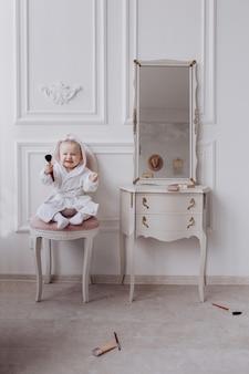 Милая маленькая женщина держит макияж кисти и весело дома. девочка сидит на стуле возле классического зеркала в помещении. детская мода. маленькая модница