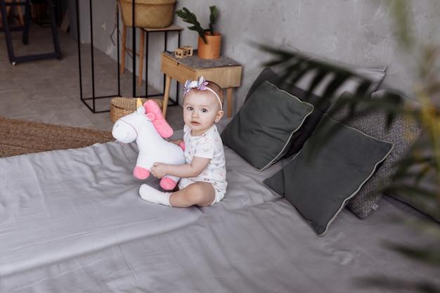 愛らしい小さな女性が自宅のベッドでおもちゃのユニコーンで遊んでいます。子供の日の概念。幸せな赤ちゃん、家族の日
