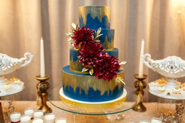 砂漠のお祝いテーブルの花の地位によって飾られた青いウエディングケーキ