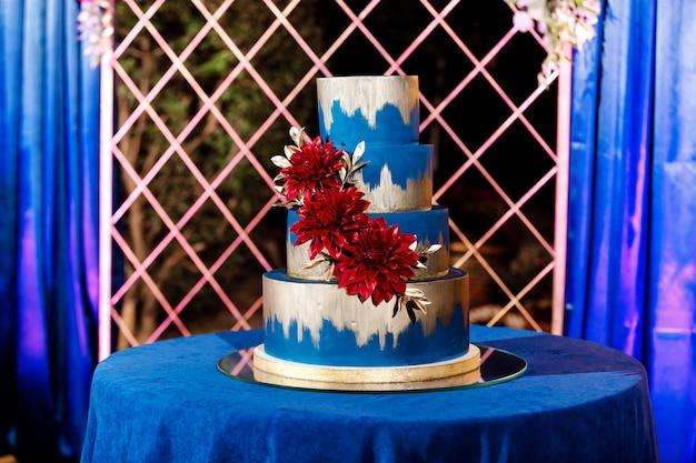 花と白いウェディングケーキのクローズアップ。大きなウエディングケーキ。インテリアトレンド結婚式。