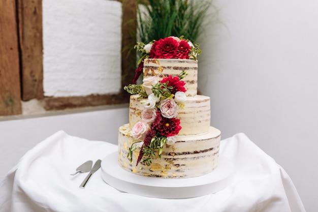 テーブルの上のウェディングケーキ。美しいカラフルな甘いウェディングケーキのカップケーキの装飾
