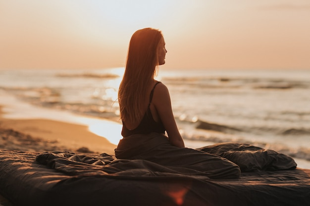 海での素敵な朝の日の出、日没の女の子のシルエット。女性は海でリラックスします。瞑想の概念