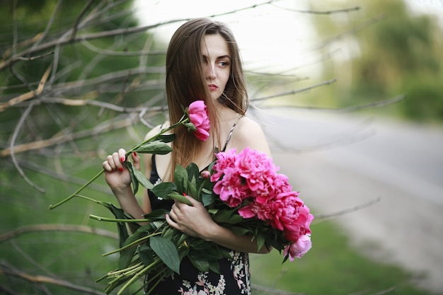 女の子は花と花束を抱擁します。牡丹のブーケ。花の中の少女。帽子の少女は深紅色の牡丹の大きな花束を押します。