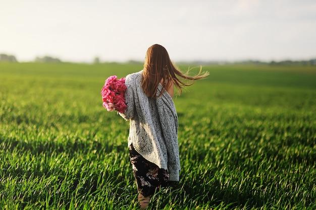 散歩、花の中の少女の美しい若い女性。牡丹のブーケ。ゴージャスな髪を持つエレガントな若い女性。牡丹を持つ少女が畑を歩きます。