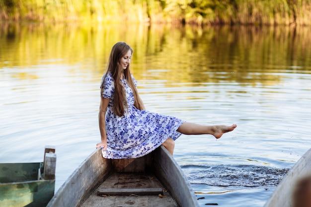 モーターボートに座っている若い美しい女性のライフスタイルの肖像画。水上ボートで楽しんでいる女の子。女の子は湖でボートに座っています。