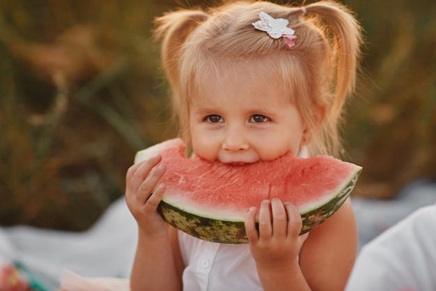 庭でスイカを食べる子。子供たちは屋外で果物を食べます。子供のための健康的なおやつ。小さな女の子がスイカのスライスを保持している庭で遊んでいます。子供の園芸