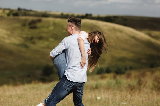 Молодая пара эмоционально веселиться, целоваться и обниматься на открытом воздухе. веселиться вместе