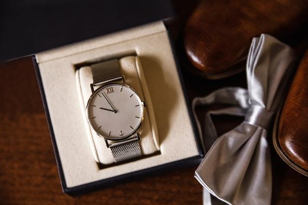 Мужские часы на столе с туфлями и бабочкой.