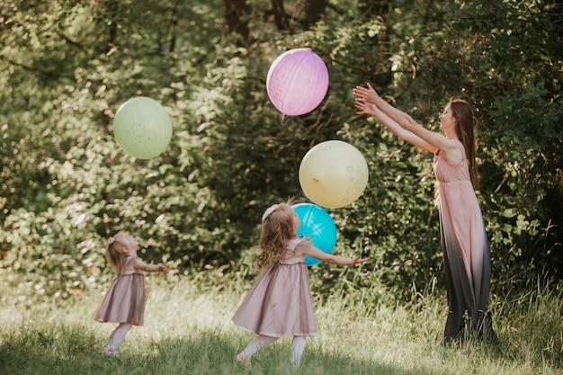 母と二人の娘が手を取り合って旋回します。一緒に家族で過ごす。風船を持つ女の子。ソフトフォーカス面白い時間