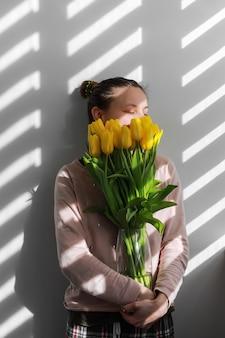 チューリップを持つ女性。黄色の花チューリップ自然の肖像画のライフスタイルを持つ若い女性