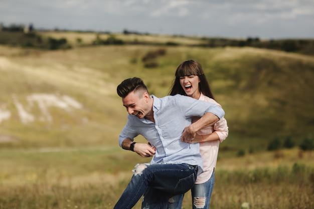 感情的に楽しんで、キスをし、屋外を抱いて狂気の若いカップル。一緒に楽しんで