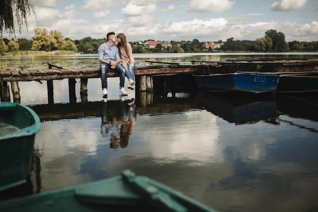 理想的な瞬間です。美しい若いカップルを受け入れ、桟橋に座っている笑顔
