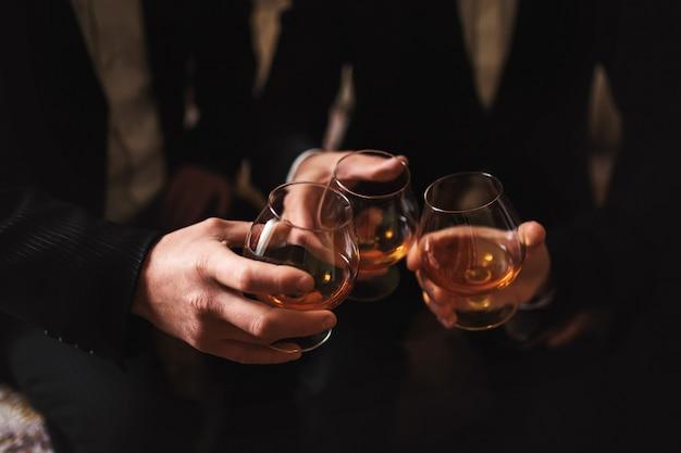 男性はウイスキーのグラスを握る