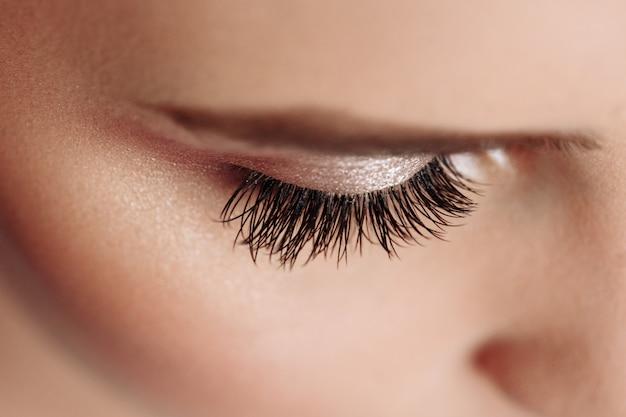 長い黒まつげ。美しい女性の眉毛と偽まつげと大きな目のクローズアップ。美容化粧品。