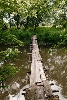 古い木製の橋、小さな川を渡る木製の橋、自然と橋。川を渡る木製の橋