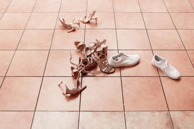 女性のカジュアルで豪華な靴。床に女性の靴。タイルの上に敷設する履物。非常に多くの異なる靴。