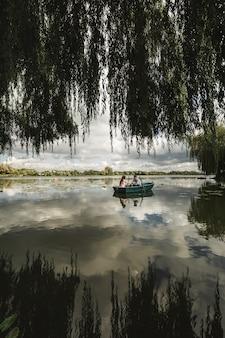 リラックスしているだけ。ボートをこいでいる間ロマンチックなデートを楽しんでいる美しい若いカップル。緑のボートに乗っている間湖で休んでいる愛情のあるカップル。ロマンス。