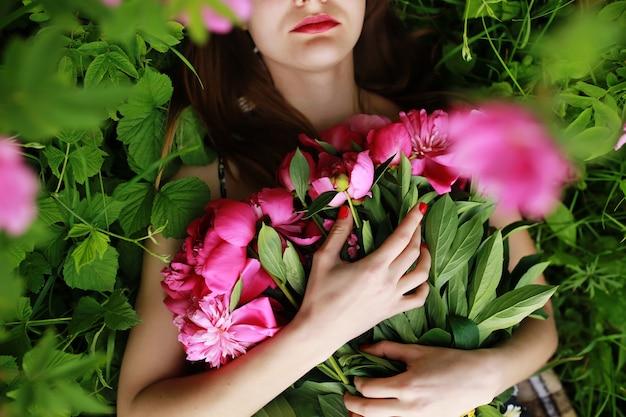 牡丹の花束。美しい若い女性は牡丹にあります。休日とイベント。バレンタイン・デー。春の花。