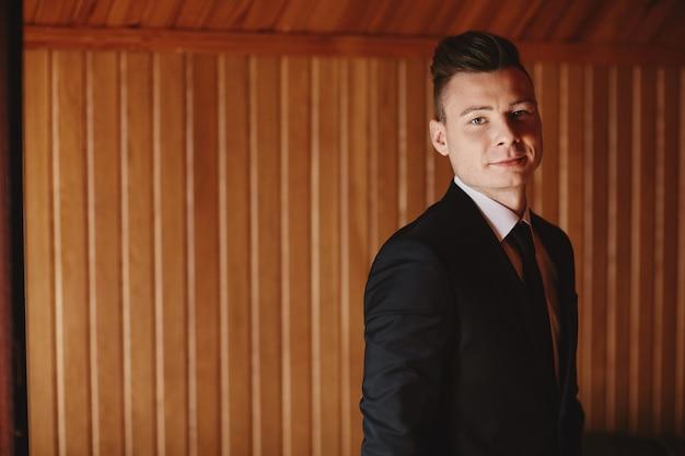 クラシックな木製のインテリアが施された豪華なアパートメントで、スーツを着た男の格好をしてください。