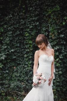 エレガントなドレスの若い美しい花嫁は、森の近くのフィールドに立って、ピンクの花と緑の花束を自然にリボンで保持しています。屋外。結婚式の後。
