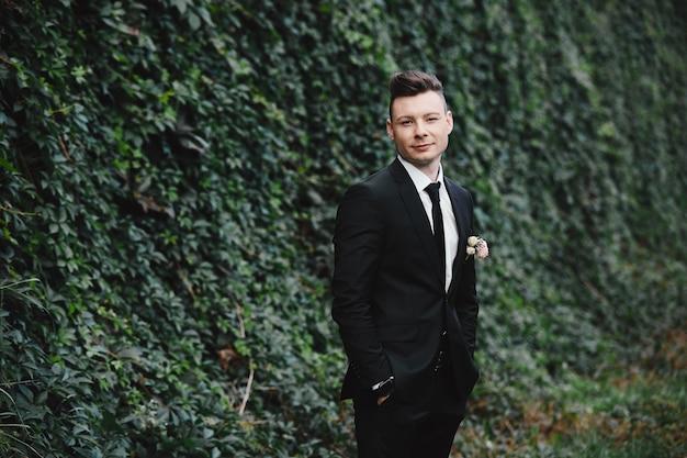 男のスタイル。エレガントな若い男。豪華な古典的なトレンディなスーツを着た男のクローズアップの肖像画。新郎の肖像画。男性の美しさ、ファッション。