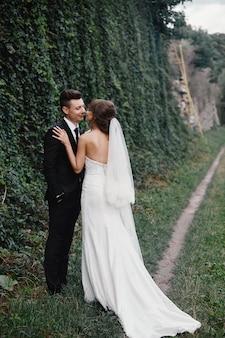 Жених и невеста в парке целуя. жених и невеста новобрачных пары на свадьбе в лесе природы зеленом целуют фото портрет. пара свадьбы. новобрачные.