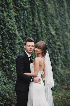 ロマンチックな幸せなカップルの新婚夫婦、新郎新婦が立って、ピンクと紫の花と緑、庭のリボンと緑の花束を保持しています。自然の結婚式。