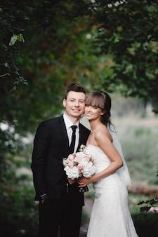 結婚式の日にスタイリッシュな新婚カップル。幸せな若い花嫁、エレガントな新郎とウェディングブーケ。自然で若い結婚式のカップルの肖像画。
