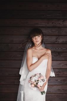 Красивая молодая улыбающаяся невеста держит большой свадебный букет с розовыми розами. свадьба в розовых и зеленых тонах. день свадьбы.