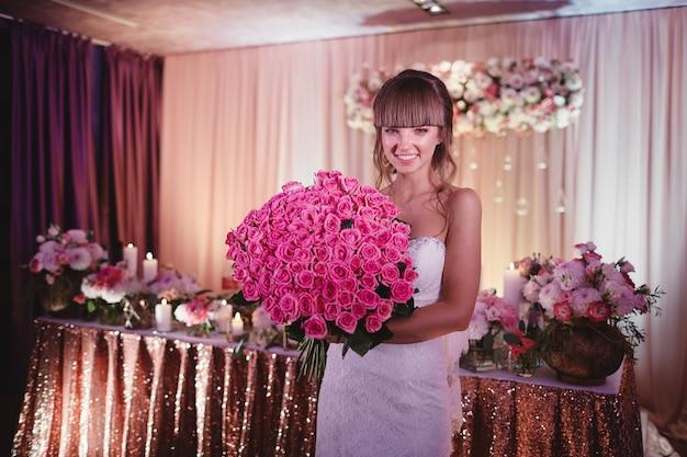 バラの大きな花束と幸せな花嫁。美しい若い笑顔の花嫁は、ピンクのバラと大きなウェディングブーケを保持しています。バラ色と緑色の色調での結婚式。結婚式。