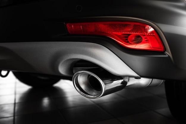 車の排気管。高級車の排気管。スタイリッシュな車のインテリア、革のインテリアの詳細。閉じる