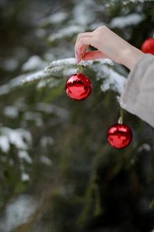 クリスマスの飾りを保持している女性。女の子は家のクリスマスツリーを飾る。休日のお祝い。季節のご挨拶