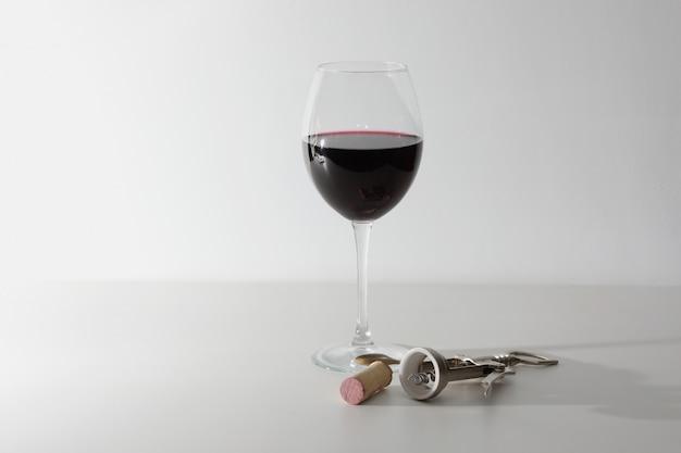 Бокал вина и некоторые винные инструменты на белой деревянной поверхности. красное вино