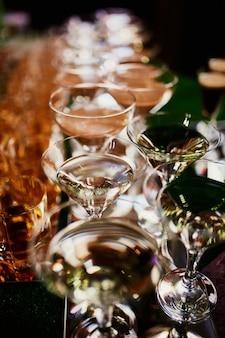 コニャックとウイスキーのグラスがバーの上に立つ。コニャックとメガネがたくさん。グラスのアルコール。バーの上に立ってさまざまなアルコール飲料。バーのコニャックとメガネ