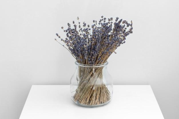 ガラス花瓶、白い木製の背景、スパのコンセプト、アロマテラピーのラベンダー色の花。ラベンダーの花のクローズアップ