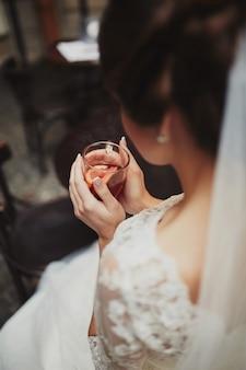 結婚式の前にお茶を飲んでいる花嫁。若い花嫁がお茶を飲みます。カフェの花嫁。