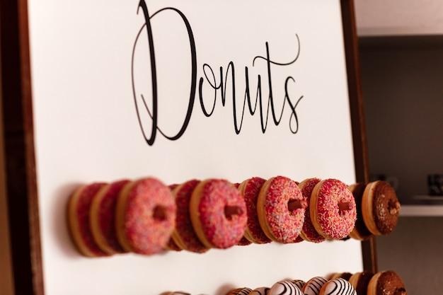 ゲスト用のウエディングチョコレートドーナツ。お祝い。結婚式の日のお菓子。結婚式のドーナツ。おいしいドーナツの壁。